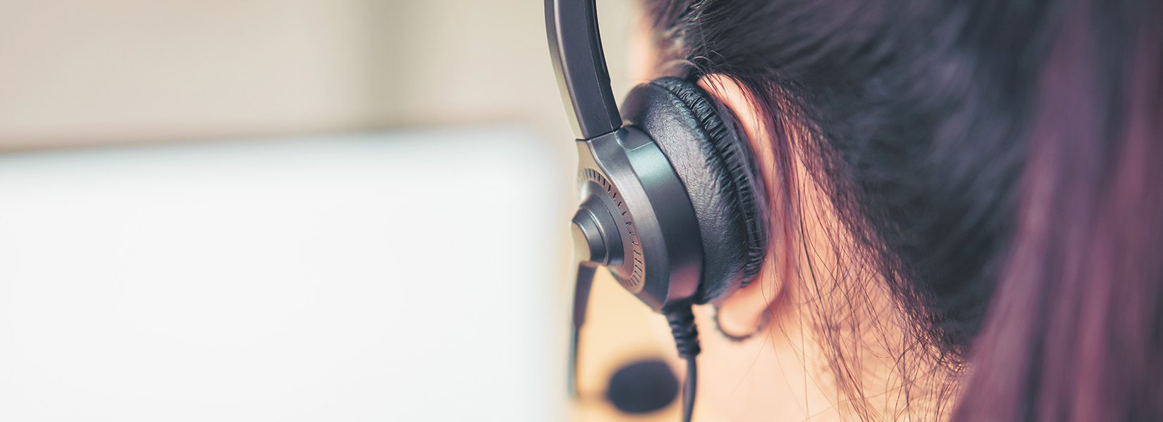 Back view of woman consultant wearing microphone headset of customer support phone operator at workplace. proportion of the banner for ads.