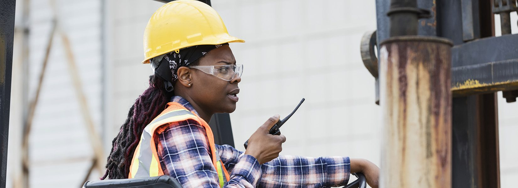A young African-American woman in her 20s operating a forklift outside a warehouse. She is wearing a hard hat, safety glasses, reflective vest and plaid shirt, sitting in the driver's seat, talking on a walkie-talkie.